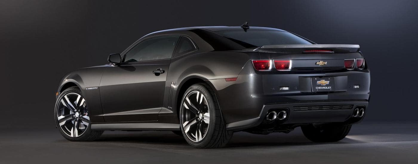A black 2012 Used Chevy Camaro is shown from behind against a black background.
