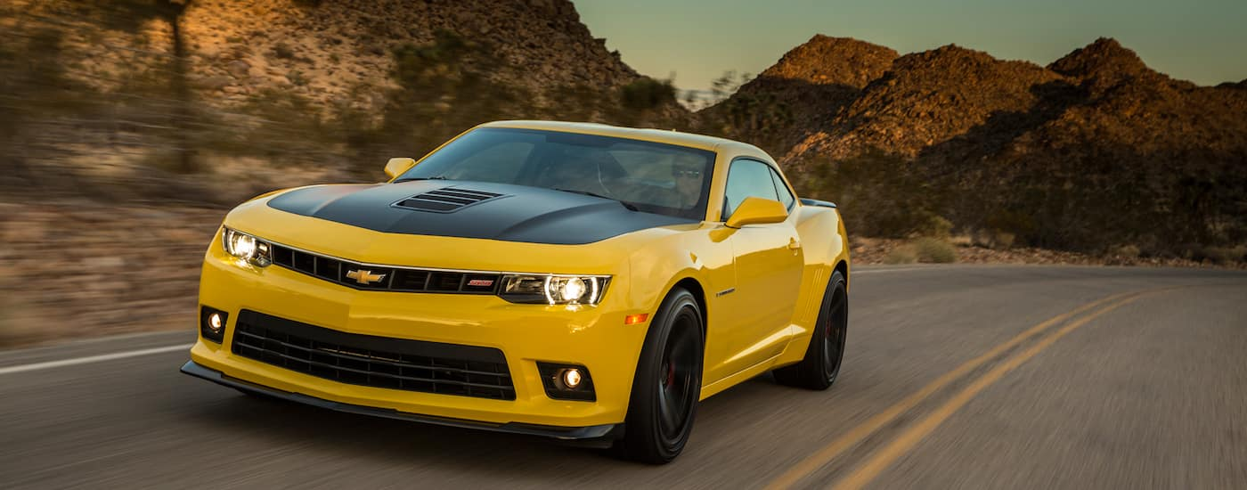 A yellow 2014 Used Chevy Camaro is driving on a desert road past mountains.