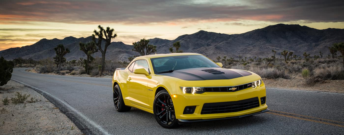 A yellow 2015 Used Chevy Camaro with a black hood is on a desert road with mountains in back.