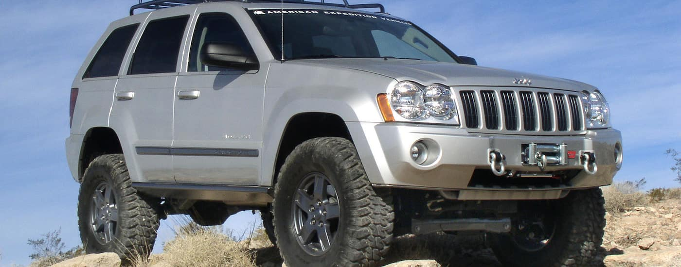 A lifted 2006 Silver Used Jeep Grand Cherokee on desert hill