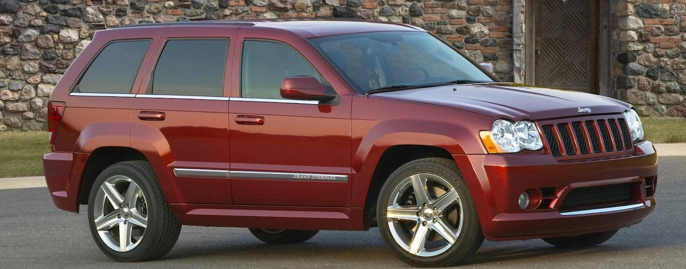 Red 2009 Used Jeep Grand Cherokee parked in front of stone house