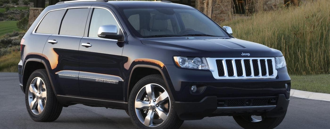 Black 2012 Used Jeep Grand Cherokee parked on street next to tall grass