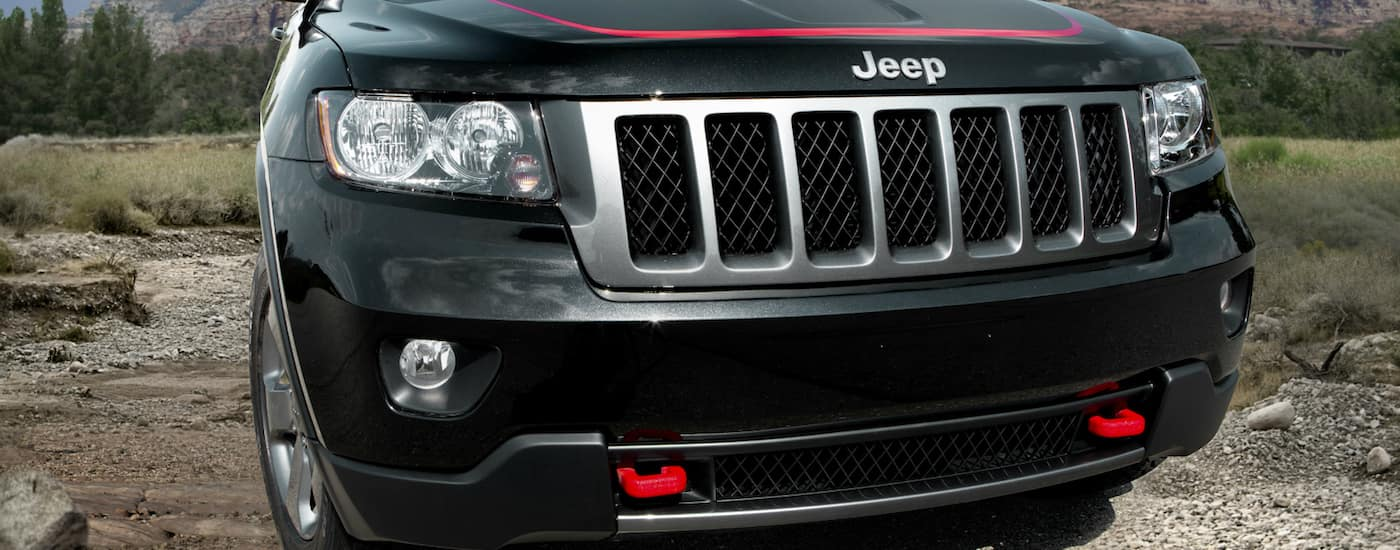 Closeup of a Black 2013 Used Jeep Grand Cherokee grille with red recovery hooks parked in mountain park