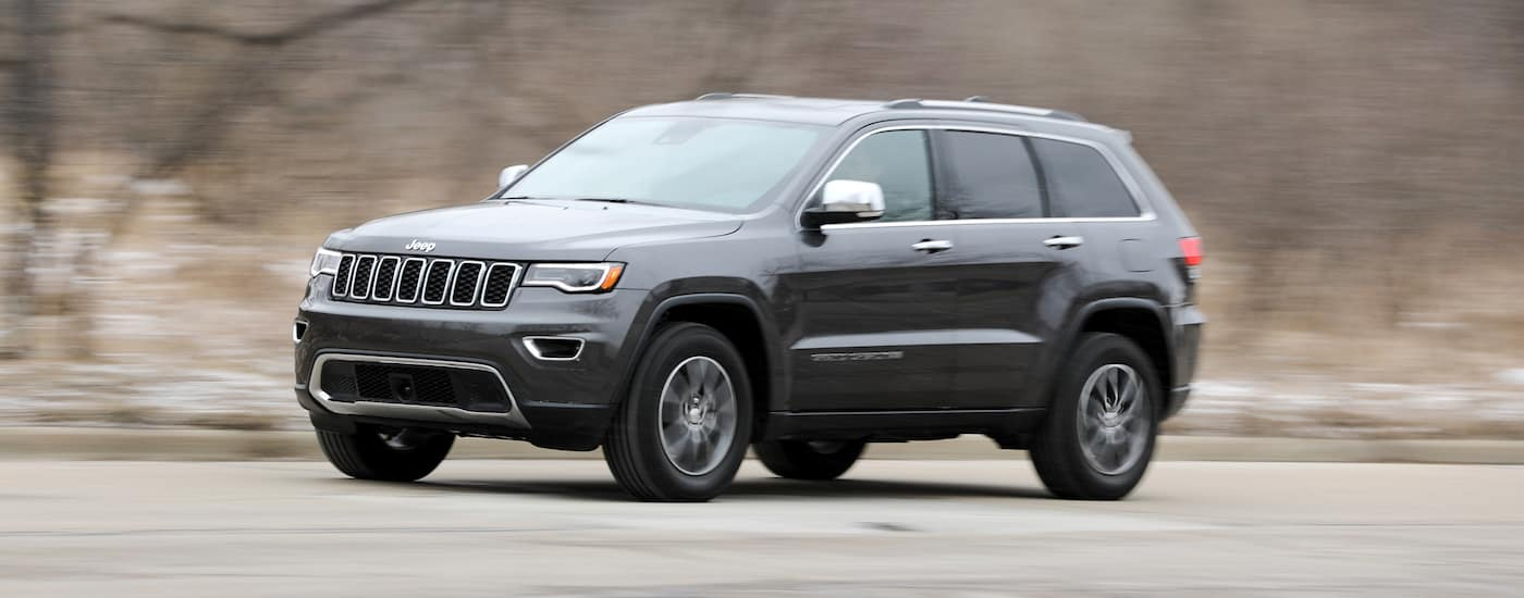 Black 2017 Used Jeep Grand Cherokee driving on the rural road