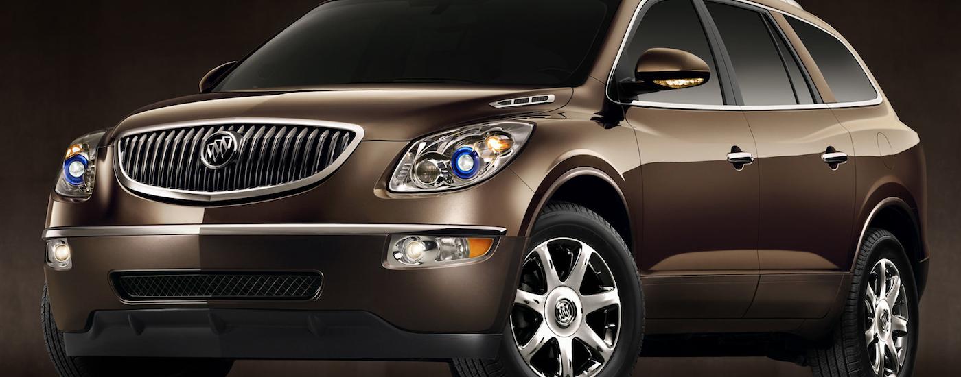 Brown/gold Used Buick Enclave angled left on a brown and black background