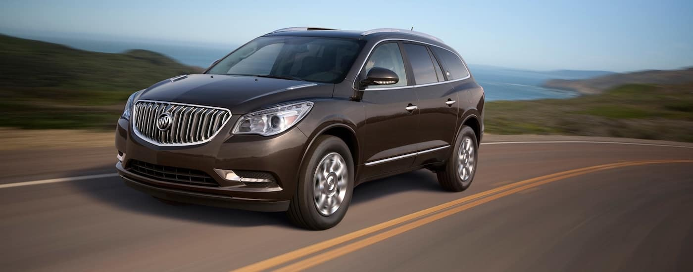 Brown Used Buick Enclave driving on an ocean-side road