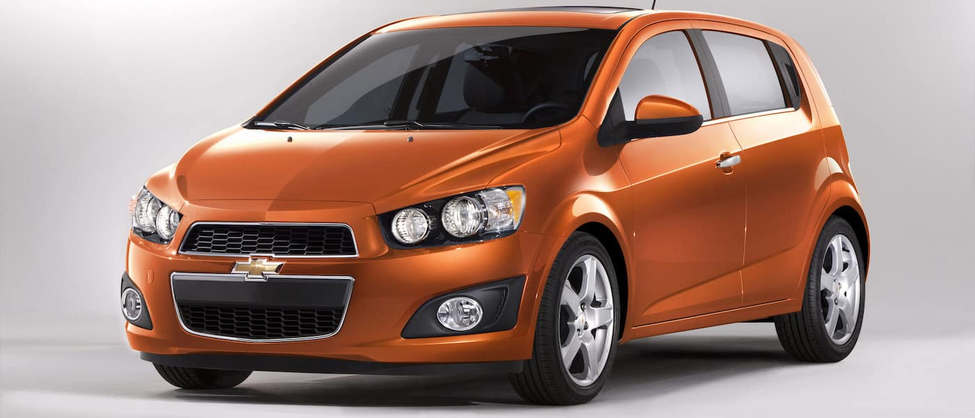 Orange Used Chevy Sonic on white