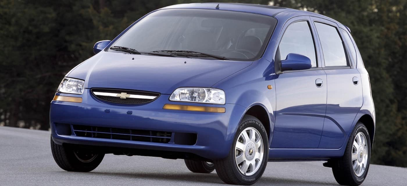 Blue Used Chevy Sonic in front of trees
