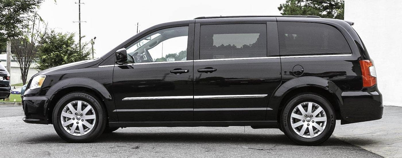 Black 2016 Used Chrysler Town & Country profile on a suburban street