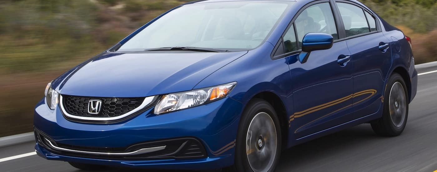 Blue 2015 Used Honda Civic driving on a country road