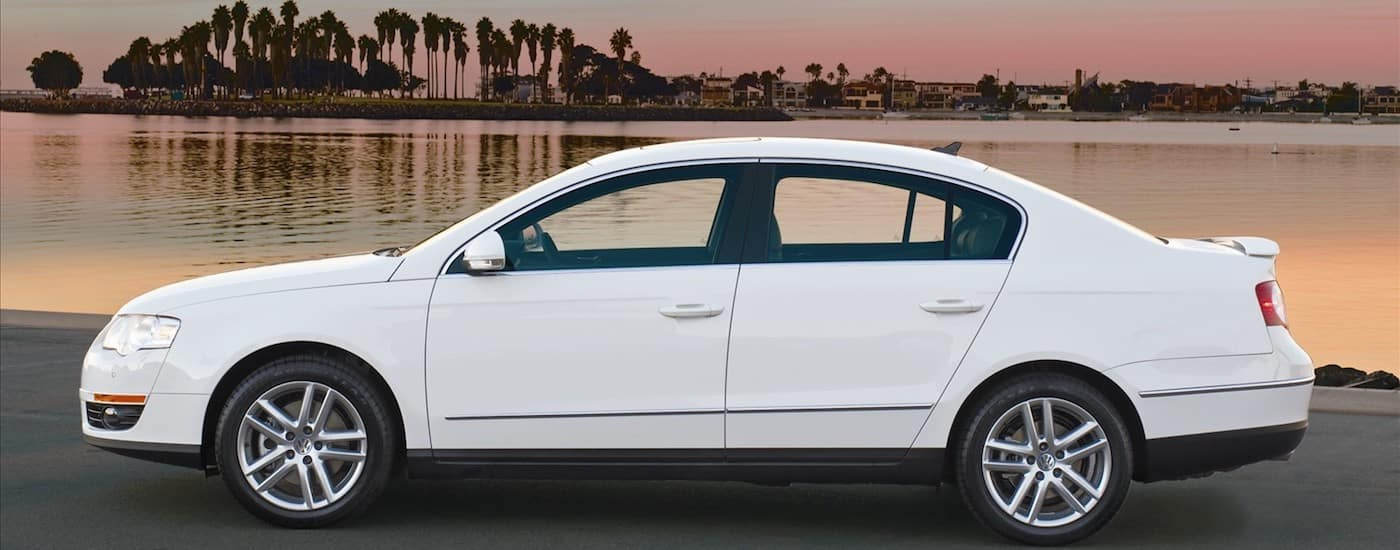 Profile of a White 2009 Used Volkswagen Passat in front of a body of water at night