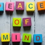 "Blue, pink, purple, yellow, and green cube letter blocks that spell out ""PEACE OF MIND"" on a grey table"