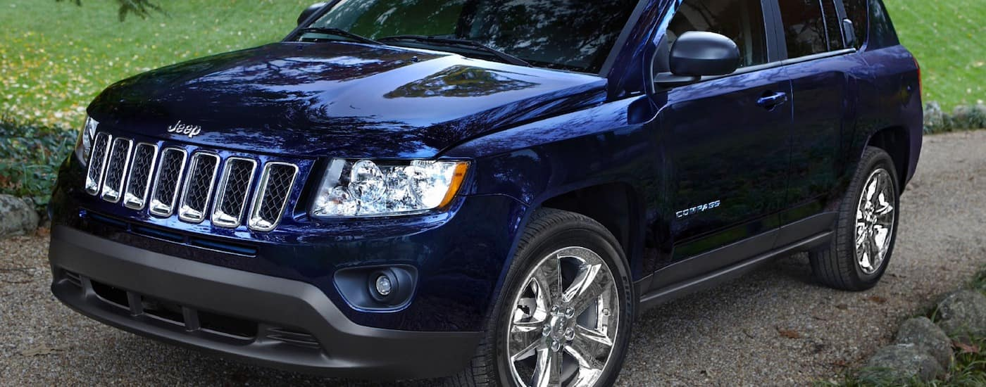 Dark blue 2013 Used Jeep Compass on a gravel road