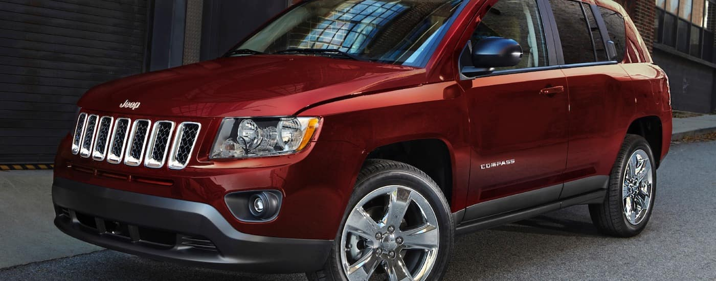 Red 2014 Used Jeep Compass parked outside a building