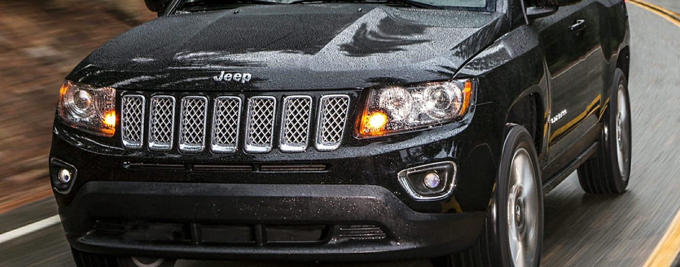 Closeup of the grille on a Black 2016 Used Jeep Compass driving in the rain