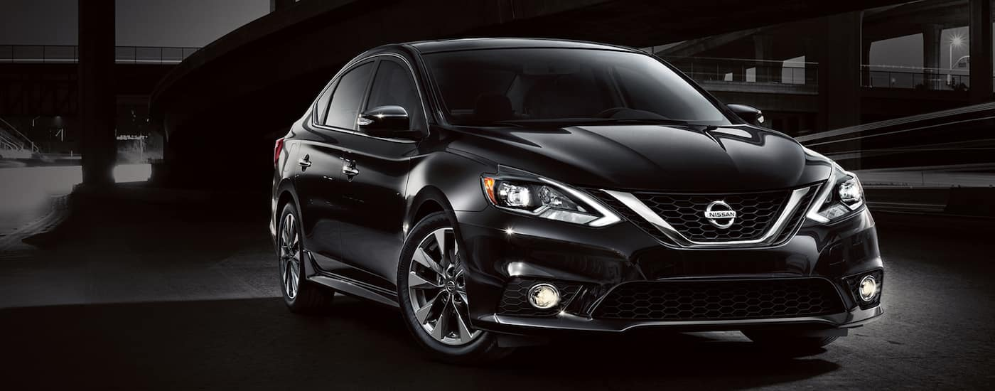 Black 2016 Used Nissan Sentra in front of a bridge at night