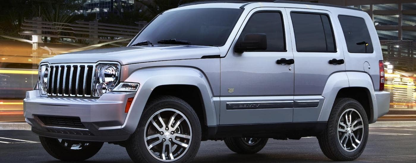 2011 Silver Used Jeep Liberty parked on a city street at night