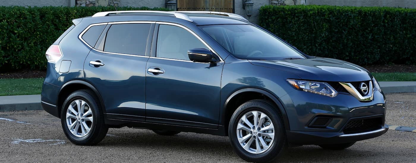 Blue 1st Generation Used Nissan Rogue in front of a hedge