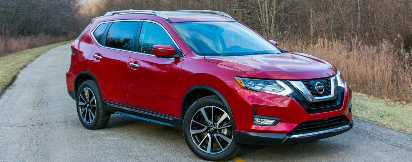 Red 2nd Generation Used Nissan Rogue on a rural road