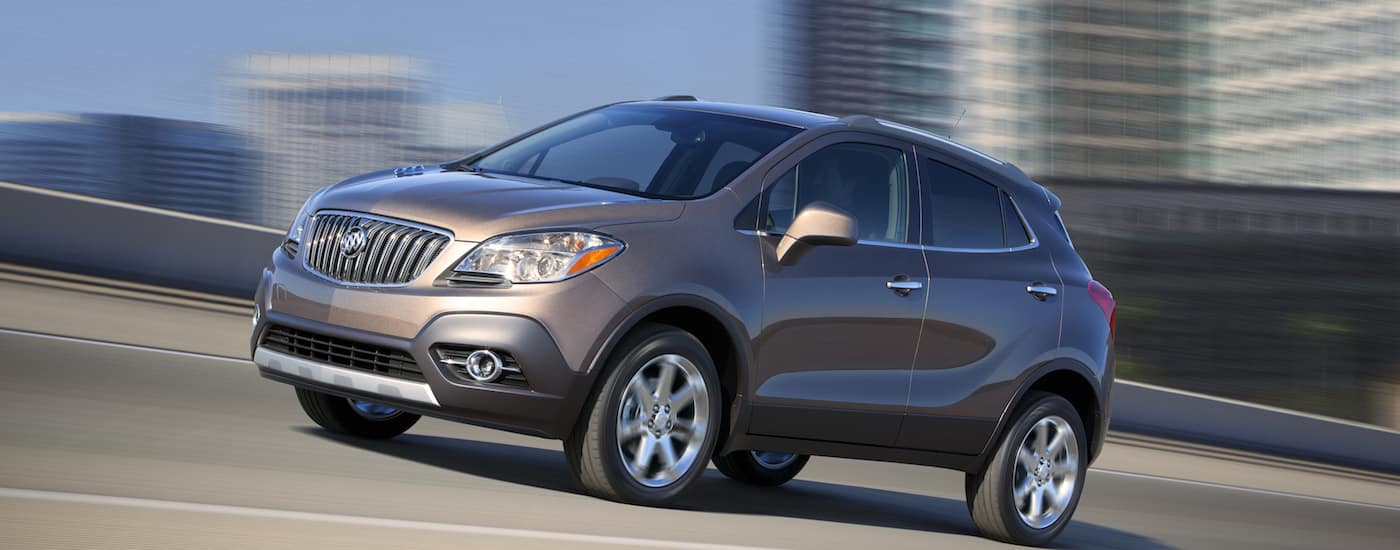 2015 Buick Encore in Cocoa Silver driving by a city