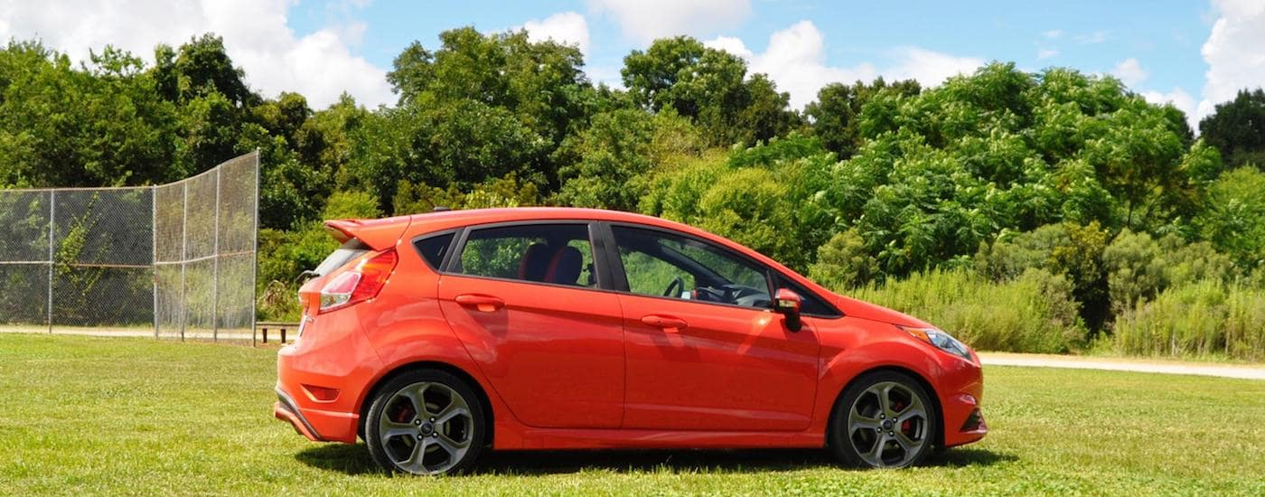 Red 2015 Used Ford Fiesta in front of a baseball field