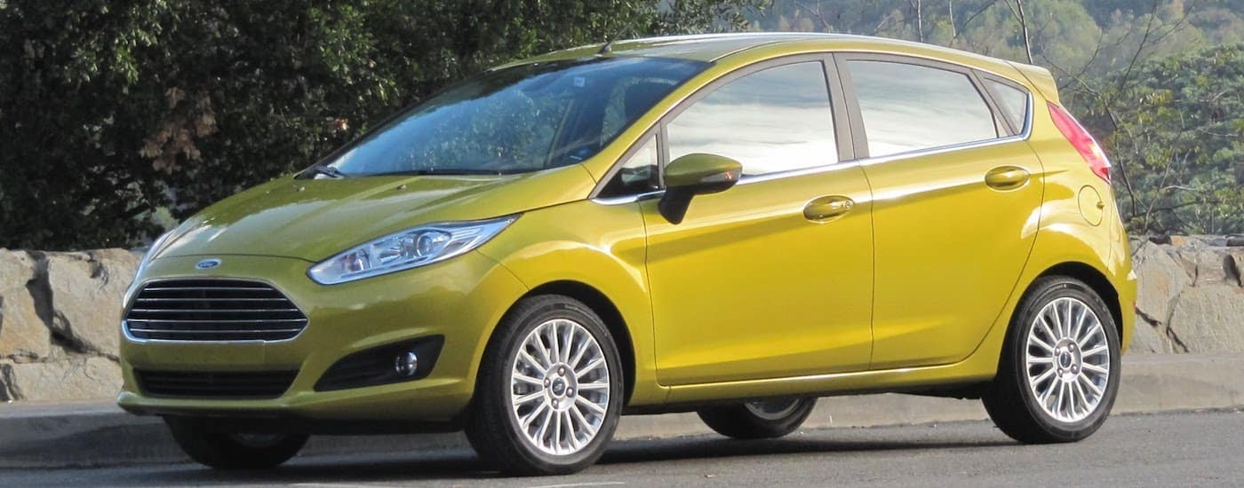 Yellow 2016 Used Ford Fiesta with trees and stone wall in back