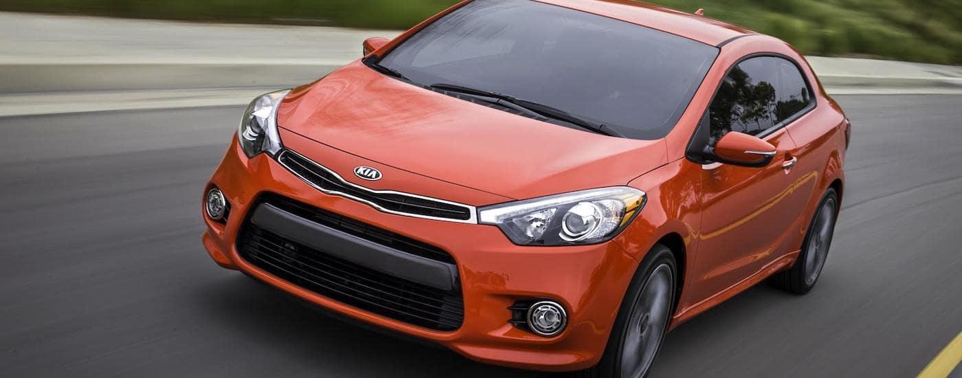 Orange 2015 Used Kia Forte driving on highway
