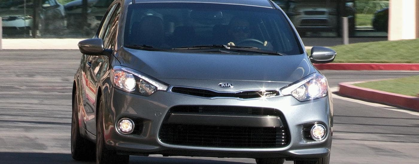 Silver 2016 Used Kia Forte from the front driving by a parking garage