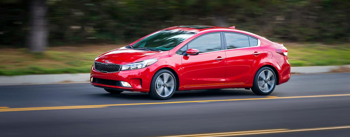 Red 2017 Used Kia Forte Sedan EX driving on a country highway