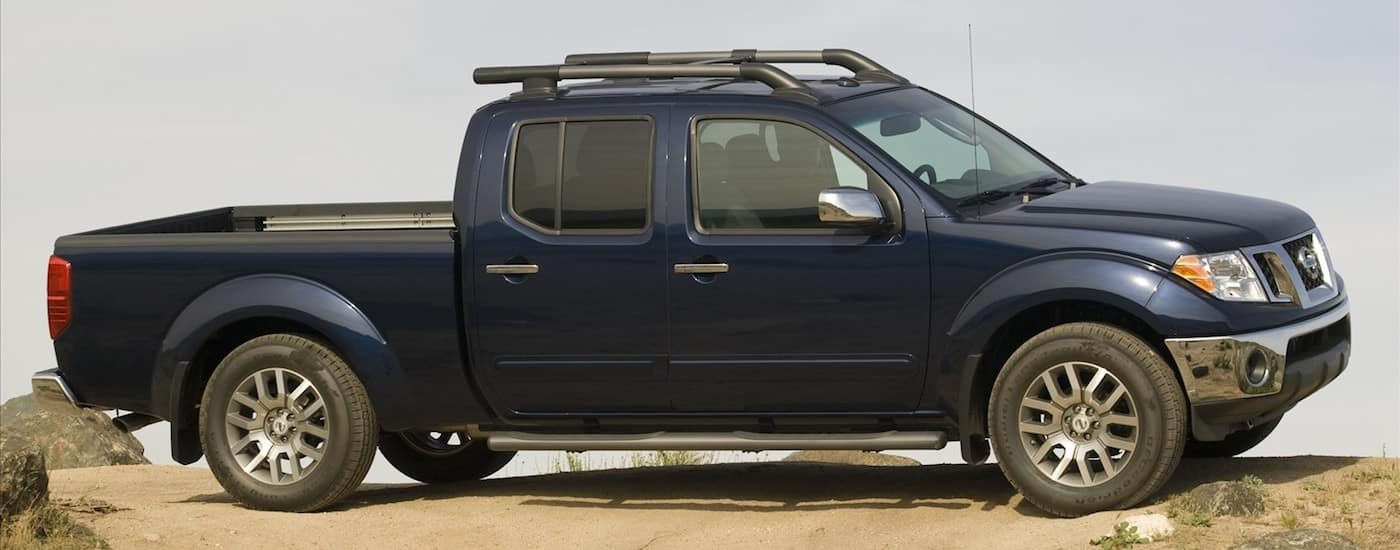 Blue 2010 Used Nissan Frontier on a desert hill