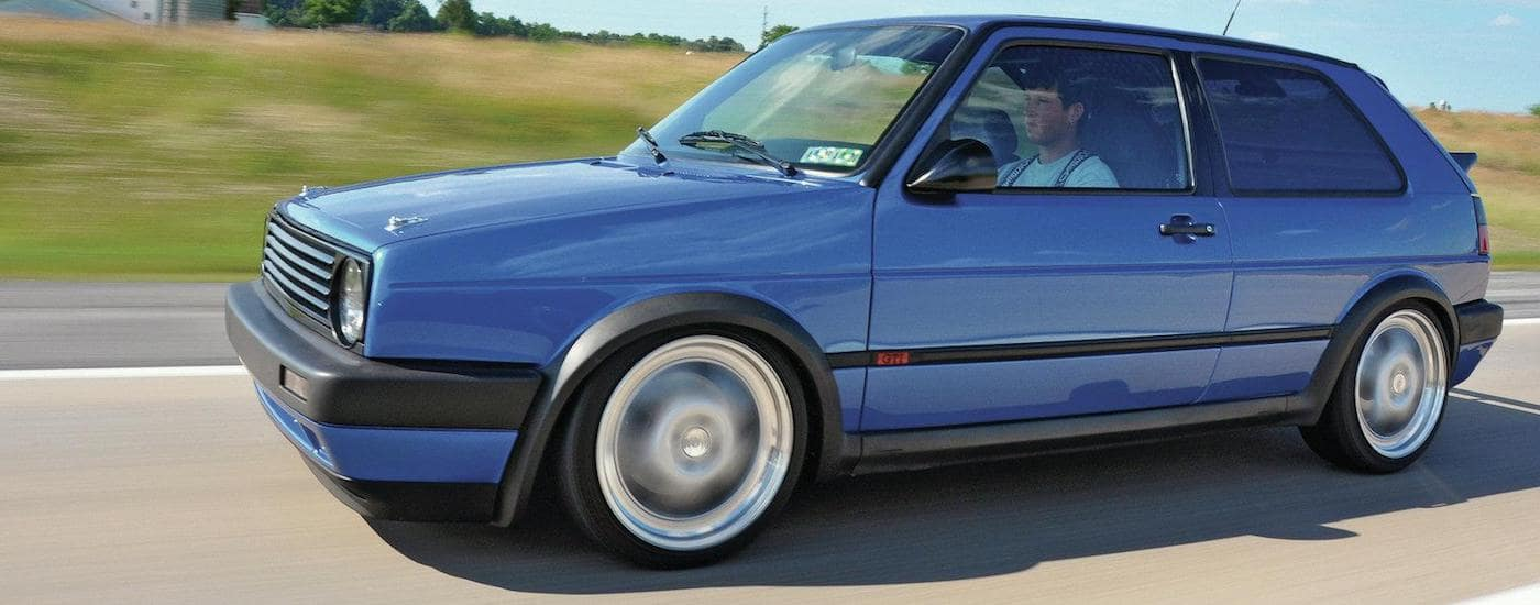 Blue 1990 Used Volkswagen Golf Driving in front of a grassy field on the Highway