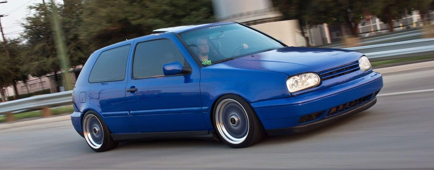 Blue 1997 Used Volkswagen Golf driving on a city street