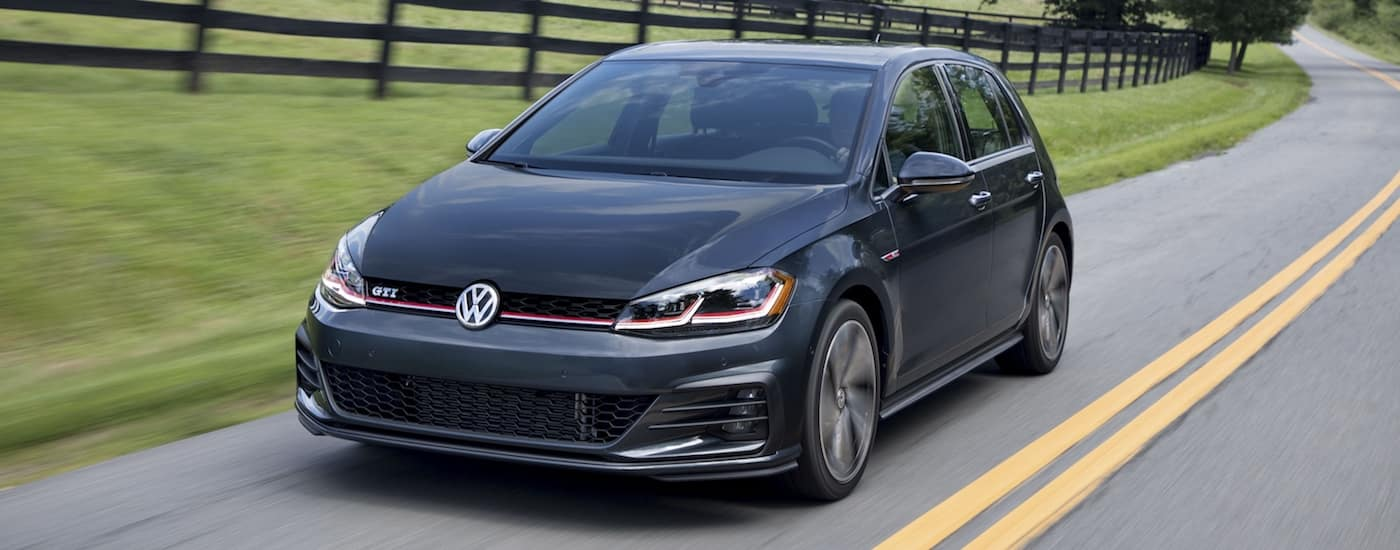 Black 2018 Volkswagen Golf Driving on the road past a black fence