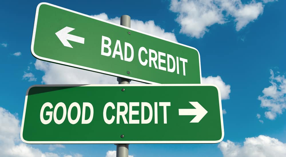 """Two green signs on top of one another, one says """"bad credit"""" with arrow pointing left, the other says """"good credit"""" with an arrow pointing right"""