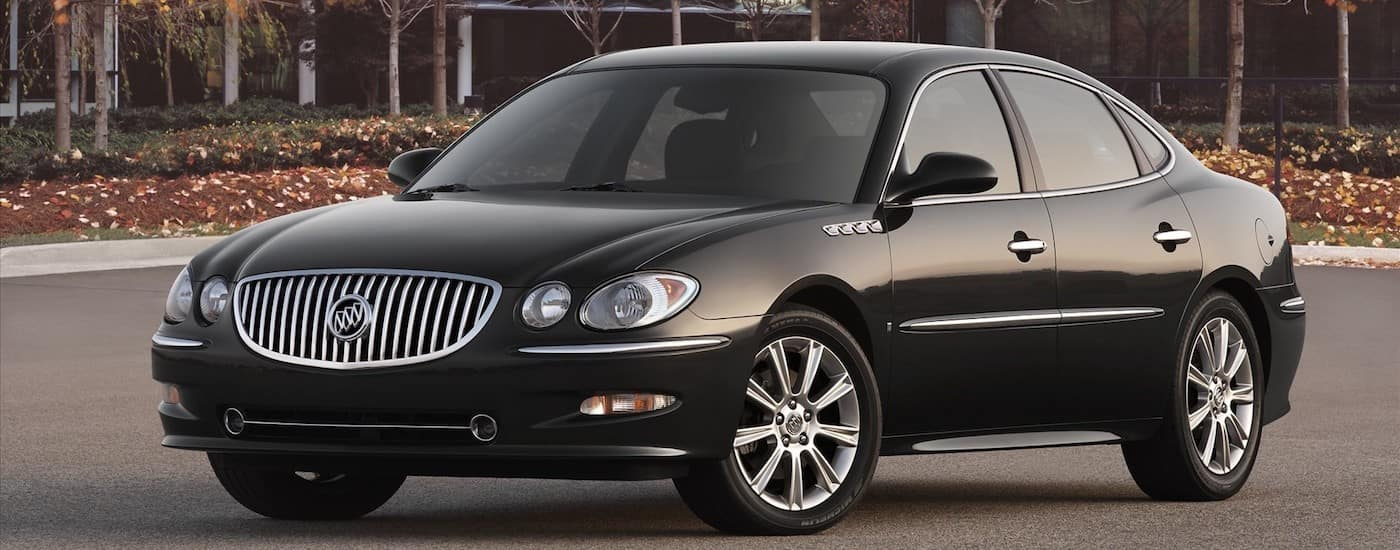 Black 2009 Used Buick LaCrosse in a parking lot with trees and buildings in distance
