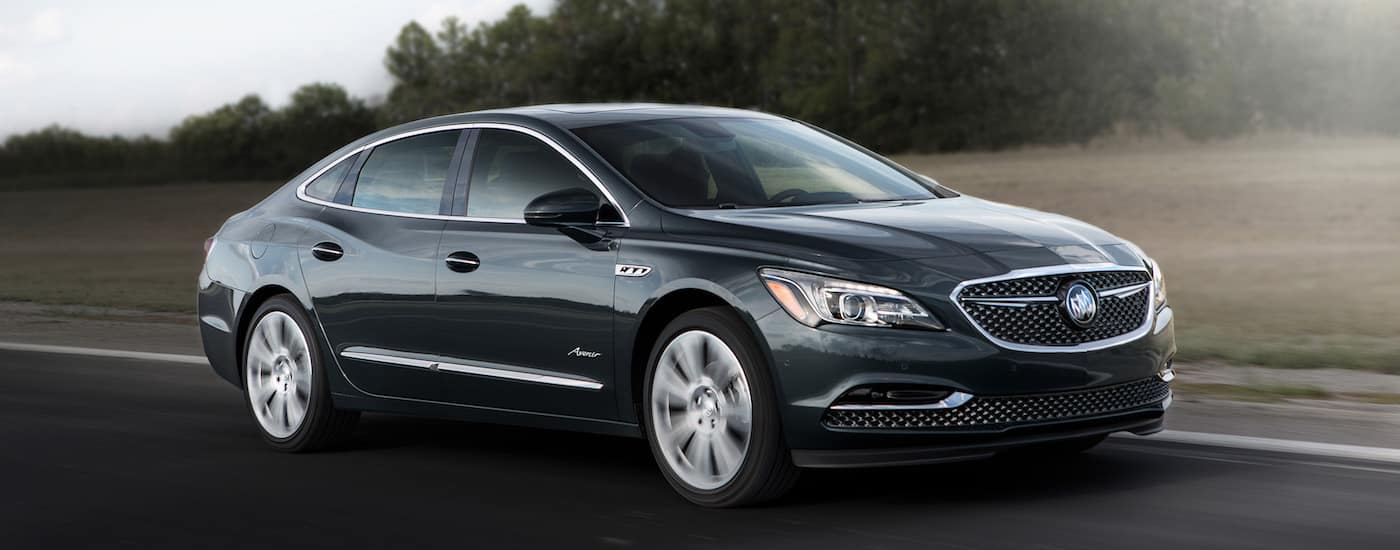 Black 2018 Buick LaCrosse Avenir driving by grassy field and trees