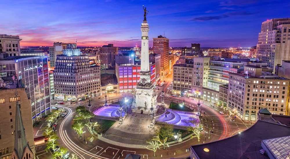 Tall Indianapolis buildings lit up and surrounding a monument