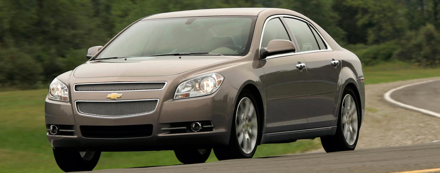 Beige 2012 Used Chevy Malibu driving on winding road
