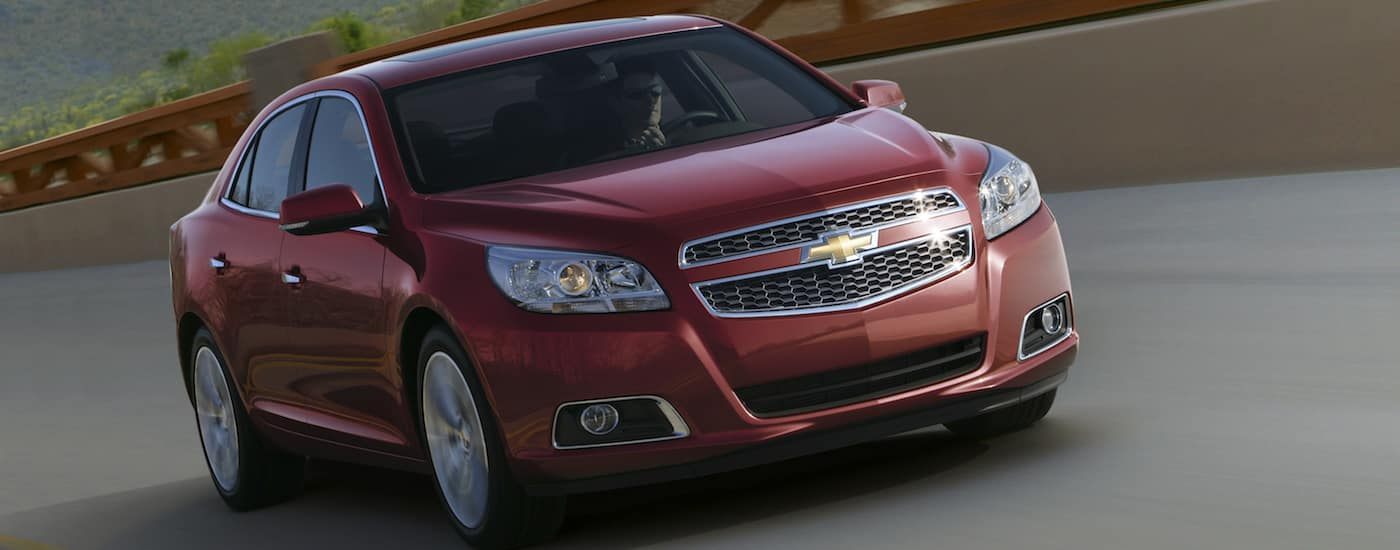 Red 2013 Used Chevrolet Malibu LTZ driving over a bridge