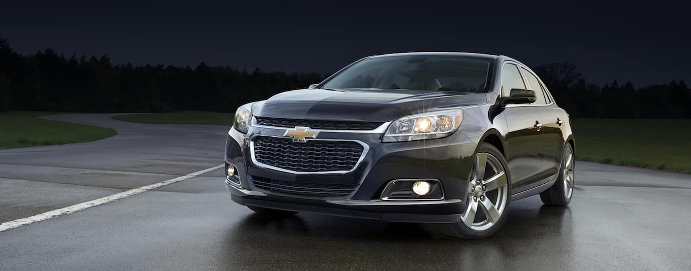 Black 2014 Used Chevy Malibu on a dark race track