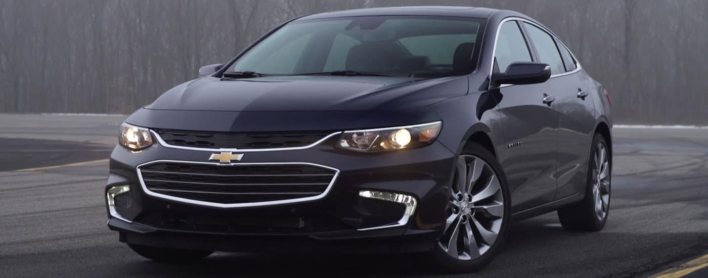 Black 2016 Used Chevy Malibu on a misty woodland road