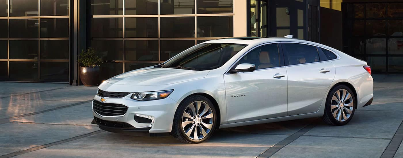 White 2017 Chevy Malibu in front a large glass windows