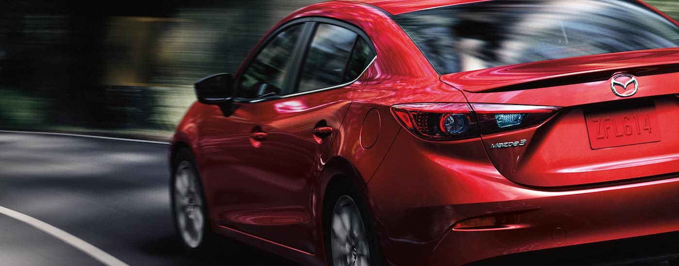 Closeup of a Red 2013 Used Mazda3 driving away on a highway