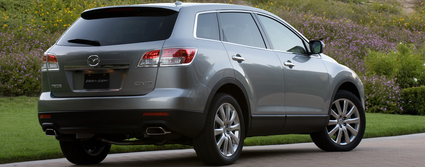 Silver 2009 Used Mazda CX-9 facing away in front of wild flowers