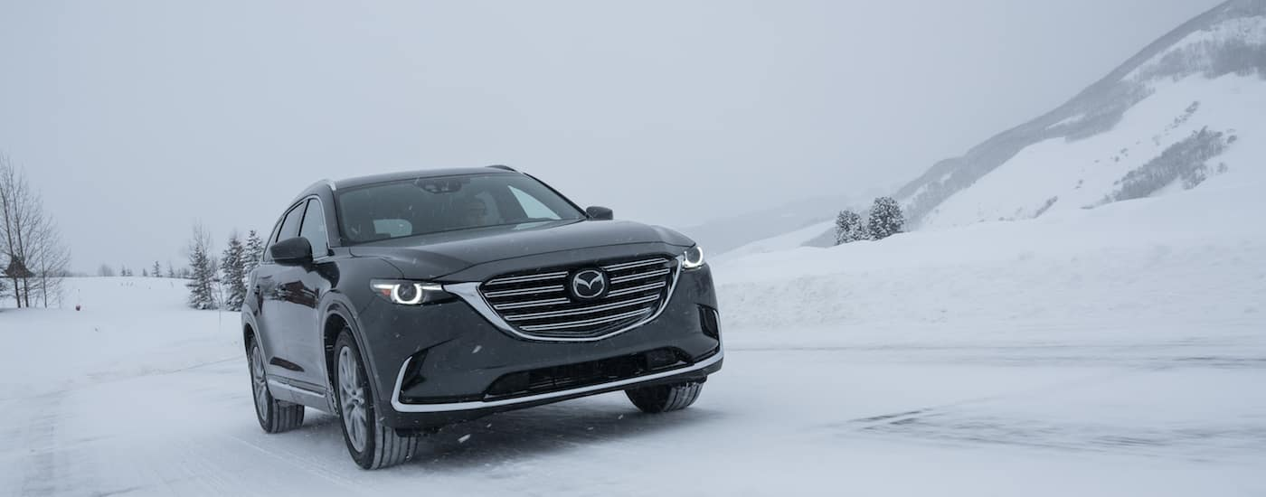 Black 2017 Used Mazda CX-9 driving in snow with mountain in back