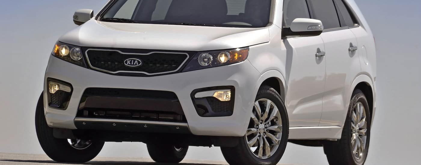 White 2012 Used Kia Sorento from the front against a pale blue sky