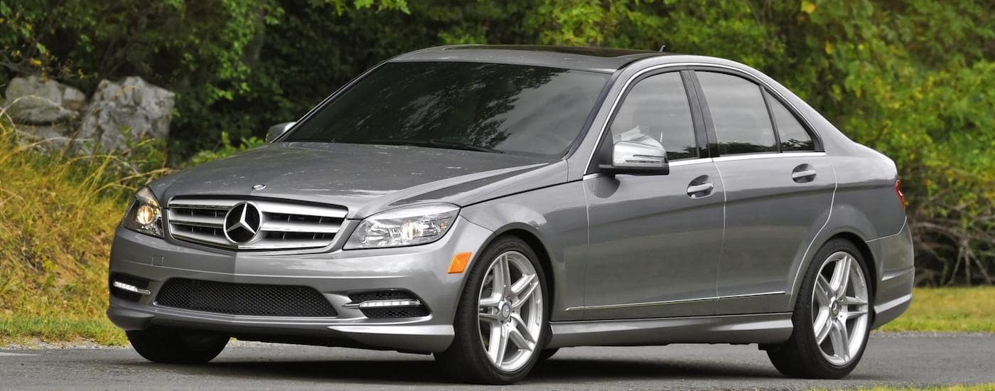 Gray 2011 Used Mercedes C-Class driving on rural road