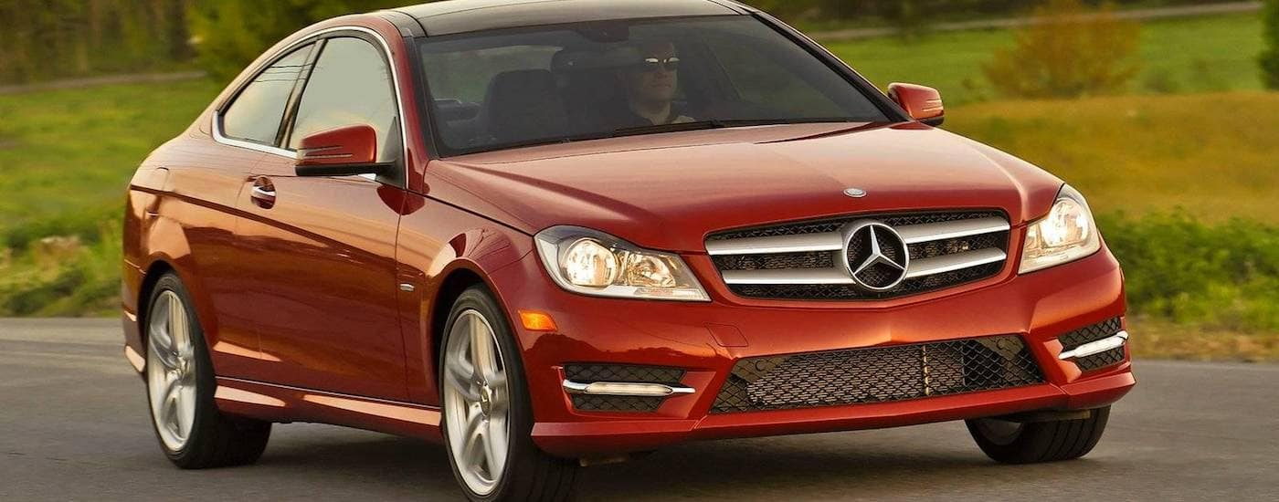 Red 2012 Used Mercedes C-Class driving in a field