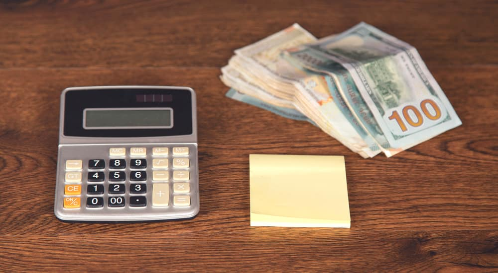 Stack of cash, yellow sticky notes, and a grey calculator sitting on a brown table
