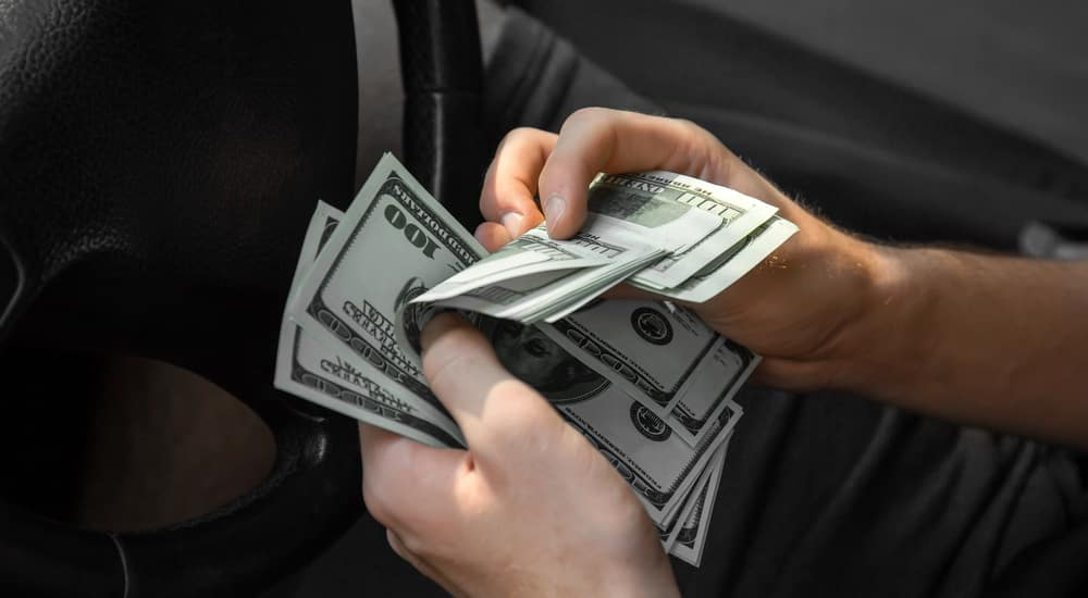 Man's hands holding and shuffling through cash in front of a black steering wheel
